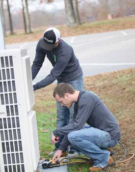 Commercial HVAC Services showing technicians repairing an outdoor commercial AC unit.